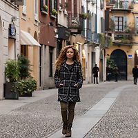 young blonde woman walking down Brera district in Milano, italy, during winter