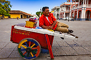 "09 JANUARY 2007 - GRANADA, NICARAGUA: A ""raspado"" vendor rests on his cart on the plaza in Granada, Nicaragua. Raspados are water and fruit juice served on shaved ice. Granada, founded in 1524, is one of the oldest cities in the Americas. Granada was relatively untouched by either the Nicaraguan revolution or the Contra War, so its colonial architecture survived relatively unscathed. It has emerged as the heart of Nicaragua's tourism revival.  Photo by Jack Kurtz"