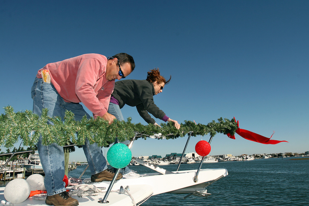 Friends and family prepare and decorate on Jim Freeman's boat before the North Carolina Holiday Flotilla at Wrightsville Beach...Photo by Logan Mock-Bunting