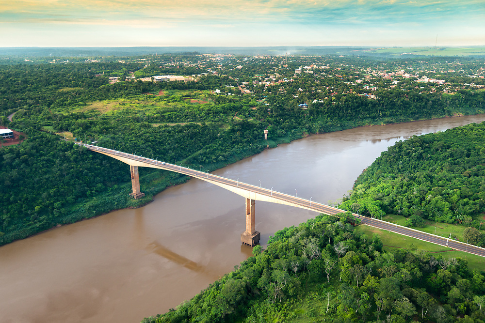 Aerial view of The Tancredo Neves Bridge, better known as Fraternity Bridge connecting Brazil and Argentina through the border over the Iguassu River, with the Argentinian city of Puerto Iguazu in the back.