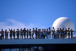 Crowd standing on the top deck of a cruise ship