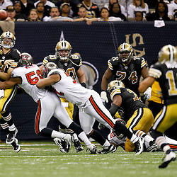 November 6, 2011; New Orleans, LA, USA; Tampa Bay Buccaneers linebacker Dekoda Watson (56) hits New Orleans Saints quarterback Drew Brees (9) as he throws to wide receiver Lance Moore (16) for a first down during the second quarter of a game at the Mercedes-Benz Superdome. Mandatory Credit: Derick E. Hingle-US PRESSWIRE