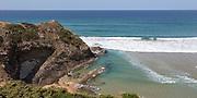 Atlantic Ocean waves breaking on rocky headland and bay with sandy beach, Praia de Odeceixe, Algarve, Portugal, Southern Europe