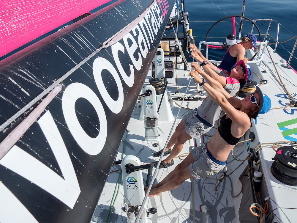 November, 2014. Leg 2 onboard Team SCA. Justine Mettraux, Stacey Jackson, and Abby Ehler attempt to flick the top batten over after a gybe in no wind.