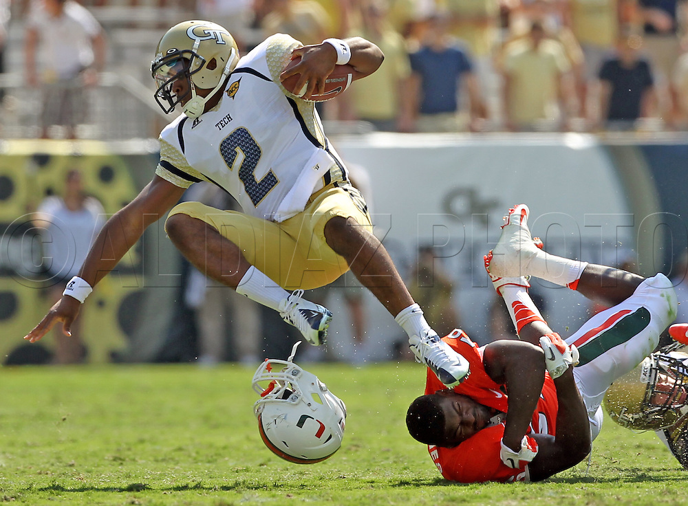 Miami's James Gains loses his helmet as he tackles Tech quarterback Vad Lee in the first quarter. Miami's The University of Miami vs Georgia Tech in football at Bobby Dodd Stadium/Grant Field in Atlanta on Saturday, September 22, 2012