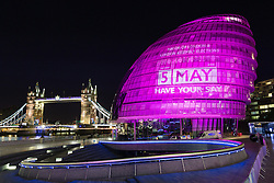 © Licensed to London News Pictures. 04/062016. LONDON, UK.  City Hall next to Tower Bridge is illuminated in hot pink, with a '5 May' calendar projection to mark the London Mayoral and local elections taking place on 5th May and remind Londoners to visit their polling stations and vote. City Hall is one of a number of landmarks across London that are being illuminated in hot pink this evening.  Photo credit: Vickie Flores/LNP