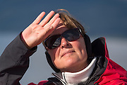 Woman shielding the sun from her eyes as she looks out.