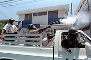 Members of the fledgling Haitian police force fire teargas to disperse rioters in Port-au-Prince, Haiti, May 1995. (Photo by Roger M. Richards)
