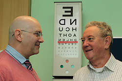 Volunteer with patient talking on front of Snellen chart in consulting room in eye clinic at QMC hospital, Nottingham.