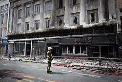 © Licensed to London News Pictures . FILE PICTURE DATED 15/07/2013 . Oldham Street , Manchester , UK . A fireman stands in front of Paul 's Hair World on Oldham Street following a fire at Paul 's Hair World on 13th July which claimed the life of fireman Stephen Hunt . Photo credit : Joel Goodman/LNP