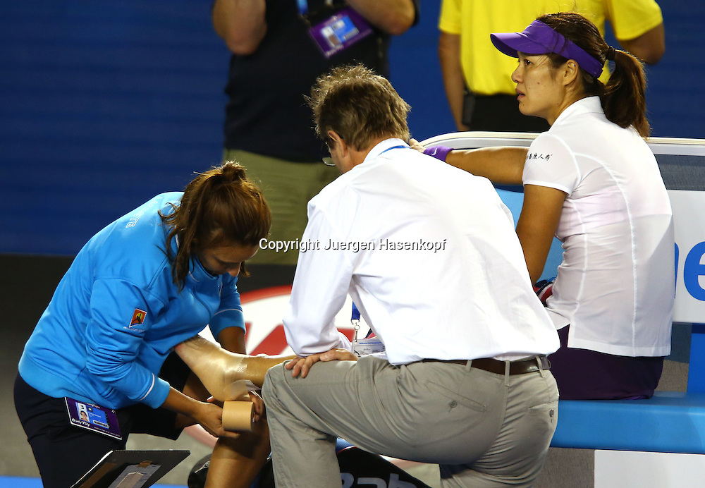 Australian Open 2013, Melbourne Park,ITF Grand Slam Tennis Tournament,Damen Einzel Endspiel, Finale, .Na Li (CHN) ist umgeknickt und wird von einer Physiotherapeutin behandelt,.Fuss wird getaped,Verletzung,Einzelbild,Ganzkoerper,Querformat,