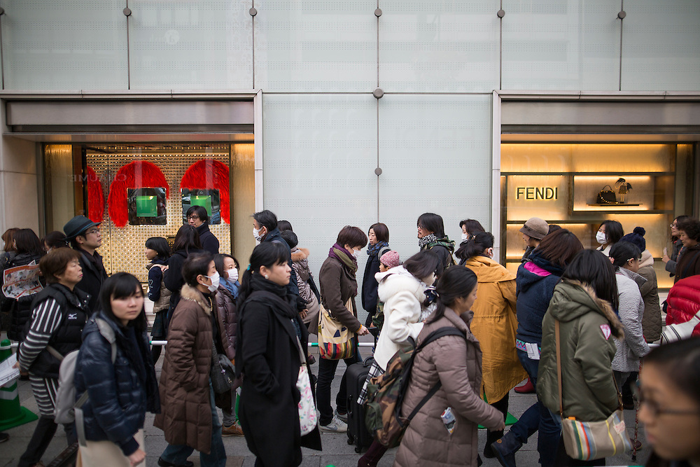 """TOKYO, JAPAN - JANUARY 2 : People wait in a queue line for the gate of Matsuya Ginza Department store to purchase the New Year's first winter sale """"Fukubukuro"""" or """"lucky bags"""" in Ginza, Tokyo on January 2, 2017. A Japanese New Year custom in which merchants make grab bags filled with unknown random contents and sell them for a substantial discounted price. (Photo by Richard Atrero de Guzman/NURPhoto)"""