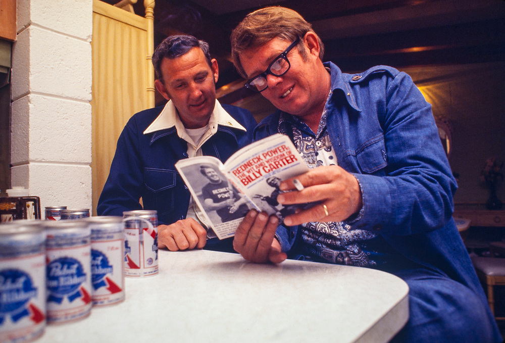 """Billy Carter and his friend Bud Duval look through a copy of """"Redneck Power - the Wit and Wisdom of Billy Carter"""". William Alton - Billy - Carter (March 29, 1937 – September 25, 1988) was an American farmer, businessman, brewer, and politician, and the younger brother of U.S. President Jimmy Carter. Carter promoted Billy Beer and was a candidate for mayor of Plains, Georgia. Carter was born in Plains, Georgia, to James Earl Carter Sr. and Lillian Gordy Carter. He was named after his paternal grandfather and great-grandfather, William Carter Sr. and William Archibald Carter Jr. respectively. He attended Emory University in Atlanta but did not complete a degree. He served four years in the United States Marine Corps, then returned to Plains to work with his brother in the family business of growing peanuts. In 1955, at the age of 18, he married Sybil Spires (b. 1939), also of Plains. They were the parents of six children: Kim, Jana, William """"Buddy"""" Carter IV, Marle, Mandy, and Earl, who was 12 years old when his father died."""