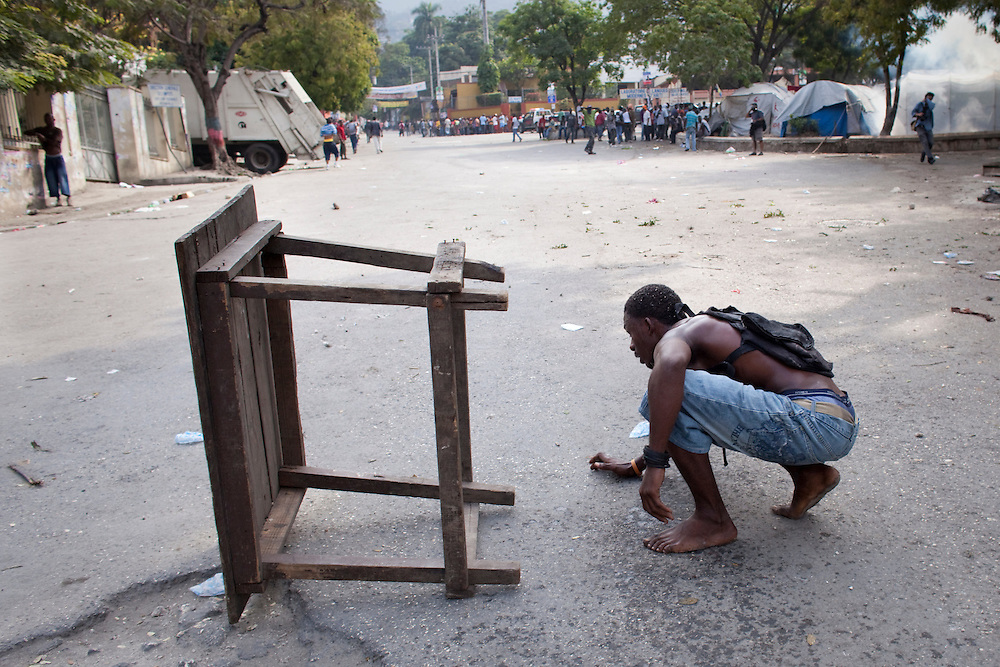 A supporters of presidential candidate Michel Martelly takes cover from UN peacekeepers behind a table during protests in Port-au-Prince, Haiti, Wednesday Dec. 8, 2010. Supporters of eliminated candidates protested after officials announced that government protege Jude Celestin and former first lady Mirlande Manigat would advance to a presidential runoff election.
