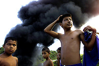 Children look on as smoke pours out of an oil pipeline that was blown up in the department of Putumayo, in southern Colombia, by rebels of the Revolutionary Armed Forces of Colombia,  FARC. The Putumayo, Colombia's principle coca growing region, is in constant turmoil as the FARC and the right-wing paramilitary group known as the United Self-Defense Forces of Colombia, AUC, battle for control of the lucrative coca fields in the region. (Photo/Scott Dalton)