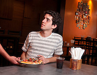 Young adult in a restauran receiving a slice of pizza.