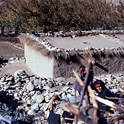 2-4 December 1976<br /> Roof line edged with brush and rows of stones. Piles of stones in mid section. Two women, one in black chader, doing something with firewood in foreground. Fields and line of tress in background.