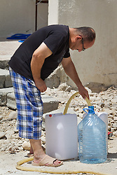 © Licensed to London News Pictures. Hamdaniyah, Iraq. 26/07/2014. An Iraqi Christian refugee from Mosul fills water containers from a tanker provided by Kurdish Zeravani soldiers in Hamdaniyah, Iraq.<br /> <br /> <br /> <br /> Having taken over Mosul Iraq's second largest city in June 2014, fighter of the Islamic State (formerly known as ISIS) have systematically expelled the cities Christian population. Despite having been present in the city for more than 1600 years, Christians in the city were given just days to either convert to Islam, pay a tax for being Christian or leave; many of those that left were also robbed at gunpoint as they passed through Islamic State checkpoints.. Photo credit : Matt Cetti-Roberts/LNP