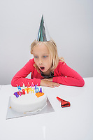 Surprised girl looking at birthday cake on table in house