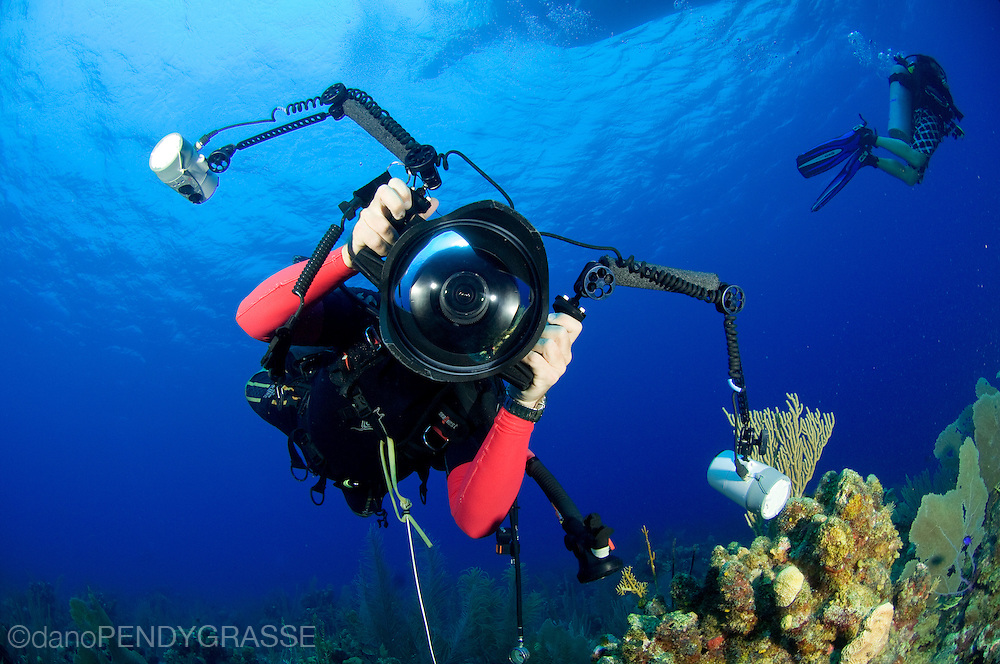 A photographer aims his underwater camera right at us.
