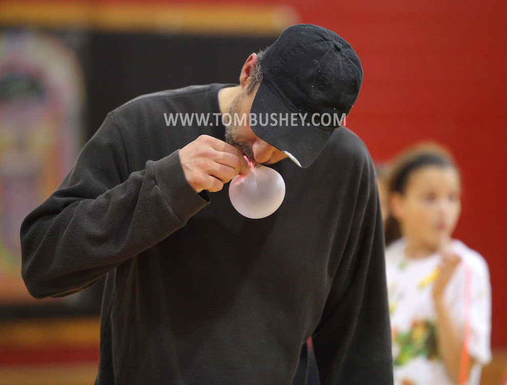 Middletown, New York - A man blows a bubble with gum during a contest at Family Night at the Middletown YMCA on April 2, 2011.