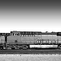 A General Electric Dash 9 stands with cargo on a train yard in the desert in Needles.