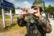 "11 JULY 2013 - RAMAN, YALA, THAILAND:   A Thai soldier uses an iPhone in a ""Hello Kitty"" holster to photograph the scene of an IED attack against members of his unit Thursday. Eight soldiers were injured when the IED exploded under a Thai Army truck carrying soldiers back to their camp after they finished a teacher protection mision. The army routinely dispatches soldiers to protect teachers and Buddhist monks, who have been targeted by Muslim insurgents as representatives of the Bangkok government. More than 5,000 people have been killed and over 9,000 hurt in more than 11,000 incidents in Thailand's three southernmost provinces and four districts of Songkhla since the insurgent violence erupted in January 2004, according to Deep South Watch, an independent research organization that monitors violence in Thailand's deep south region that borders Malaysia.  PHOTO BY JACK KURTZ"