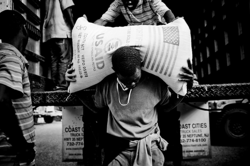 Men unload food provided by USAID for victims of the recent earthquake in Port-au-Prince, Haiti.