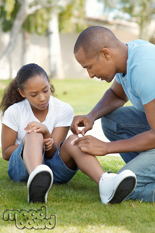 Father applying bandaid to daughter (7-9) in park