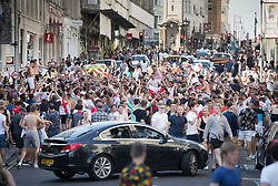 © Licensed to London News Pictures. 07/07/2018. Brighton, UK. Football fans bring traffic to a standstill on a street in Brighton as they celebrate England's 2-0 quarter-final win over Sweden at the Russian World Cup. Photo credit: Peter Macdiarmid/LNP