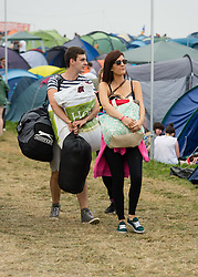 © Licensed to London News Pictures. 05/09/2014. Isle of Wight, UK. Festival goers walking through the campsite at Bestival 2014 Day 2 Friday carrying their tents having just arrived, looking for a place to pitch their tent.  This weekend's headliners include Chic featuring Nile Rodgers, Foals and Outcast Photo credit : Richard Isaac/LNP