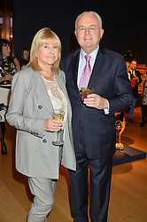 MARTYN LEWIS and his wife PATSY at a party to celebrate the publication of Interiors For Living by Joanna Wood held at Christie's. 8 King Street, St.James's, London on 2nd March 2015.