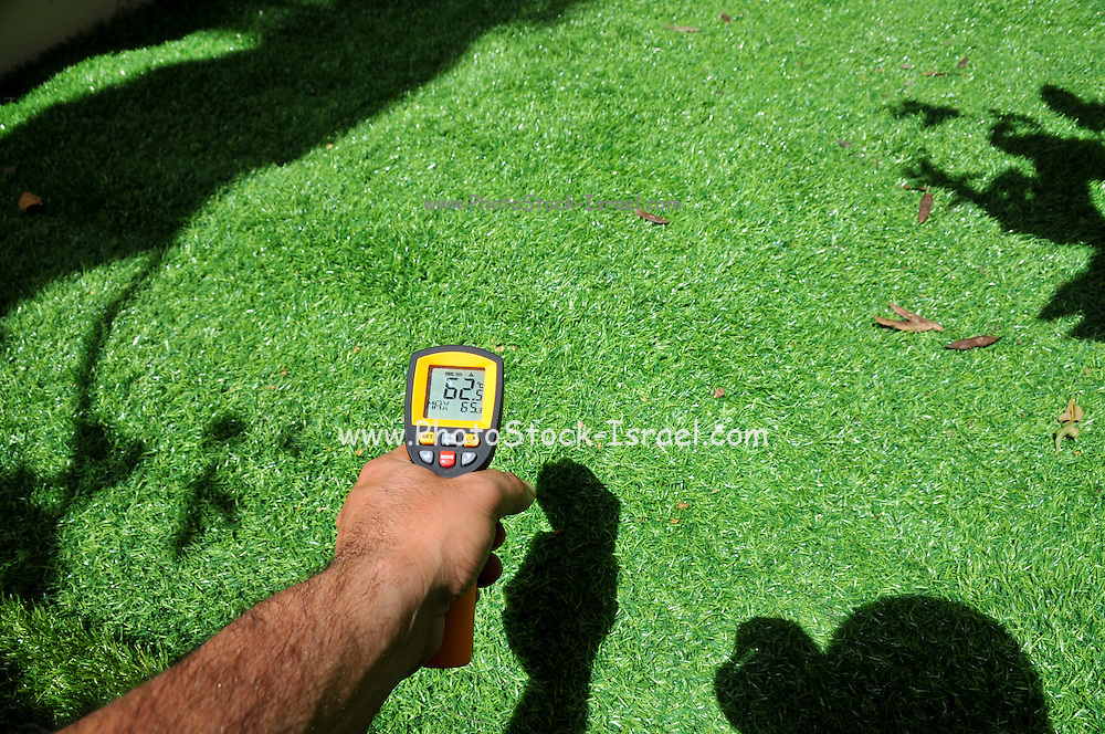 Measuring the temperature of artificial lawn in direct sun - 62 degrees Celsius