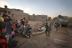 Members of the 1st Infantry, 17th Regiment, are seen talking with children, while they help Iraqi forces patrol in western Mosul, Iraq, Dec. 11, 2005. This is part of an effort to provide security in preparation for Iraq's first post-Saddam parliamentary elections. The western sector is home to Mosul's primarily Sunni population, which has been resistant to the American presence in Iraq.