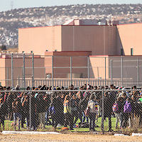 Students pack the football field where they were evacuated to following a bomb threat at Gallup High School Wednesday.