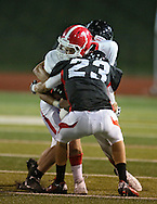 Washington's Charles Blades (7) is hit by Linn-Mar's Andrew Gassmann (23) and Austin Burbridge (15) during the second quarter of the game between Cedar Rapids Washington and Linn-Mar at Linn-Mar Stadium in Marion on Friday, September 14, 2012.