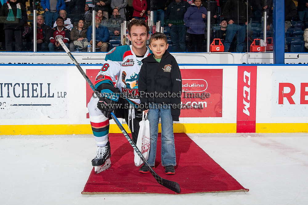 KELOWNA, CANADA - JANUARY 3: Carsen Twarynski #18 of the Kelowna Rockets stands on the ice with a young fan to accept the first star of the game against the Tri-City Americans on January 3, 2017 at Prospera Place in Kelowna, British Columbia, Canada.  (Photo by Marissa Baecker/Shoot the Breeze)  *** Local Caption ***