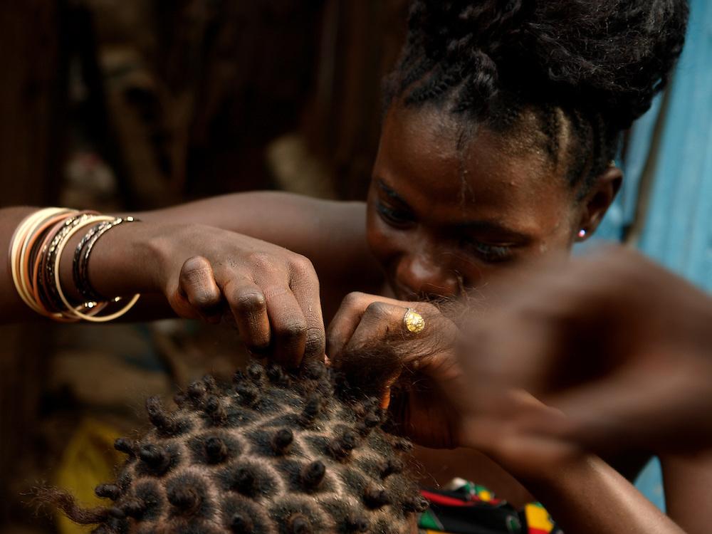 women braiding hair in kroo Bay slum. ..Kroo Bay, Freetown, Sierra Leone.