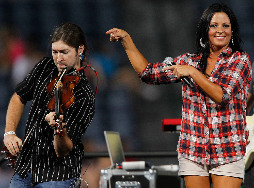 ATLANTA - AUGUST 7:  Singer Sara Evans (R) performs with mandolin player Brent Wilson (L) in a post-game concert following the Major League Baseball game between the San Francisco Giants and the Atlanta Braves at Turner Field on August 7, 2010 in Atlanta, Georgia.  (Photo by Mike Zarrilli/Getty Images)