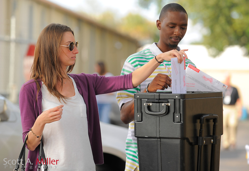 Voters places absentee ballots into a ballot box outside of the Orange County Supervisor of Elections office in Orlando, Florida November 5, 2012.  ©2012 Scott A. Miller.
