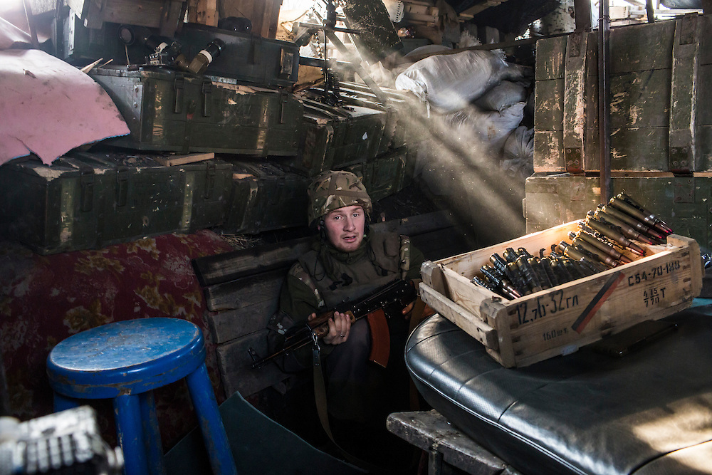 A fighter for the Dnipro-1 battalion, a pro-Ukrainian militia, sits in a front-line trench on March 20, 2015 in Pisky, Ukraine.