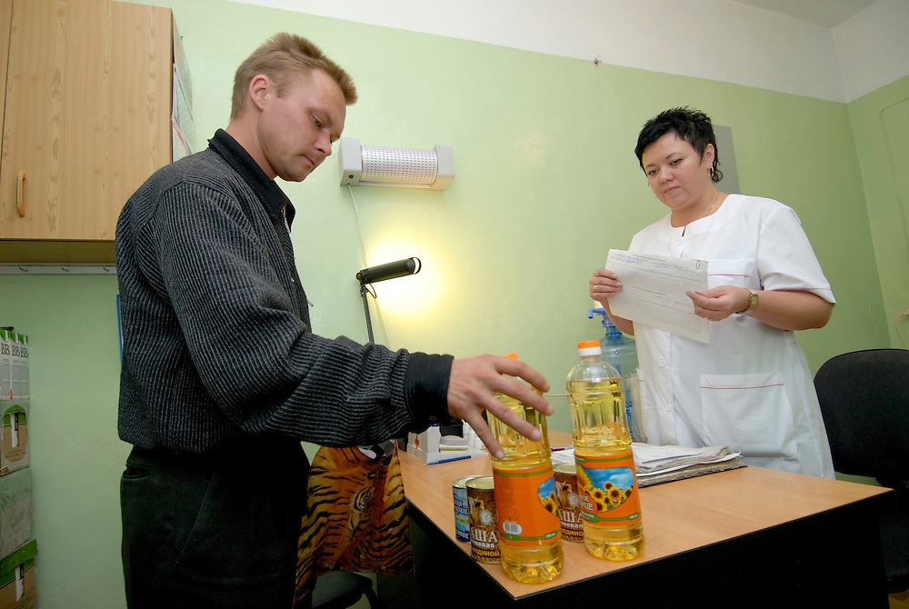 Russia.Tomsk (Siberia). 24.08.2007. Red Cross Center. A TB out-patient receiving his daily food supply. The Red Cross, through PIH and with the support of the Global Fund distributes medication and food to TB out-patients.