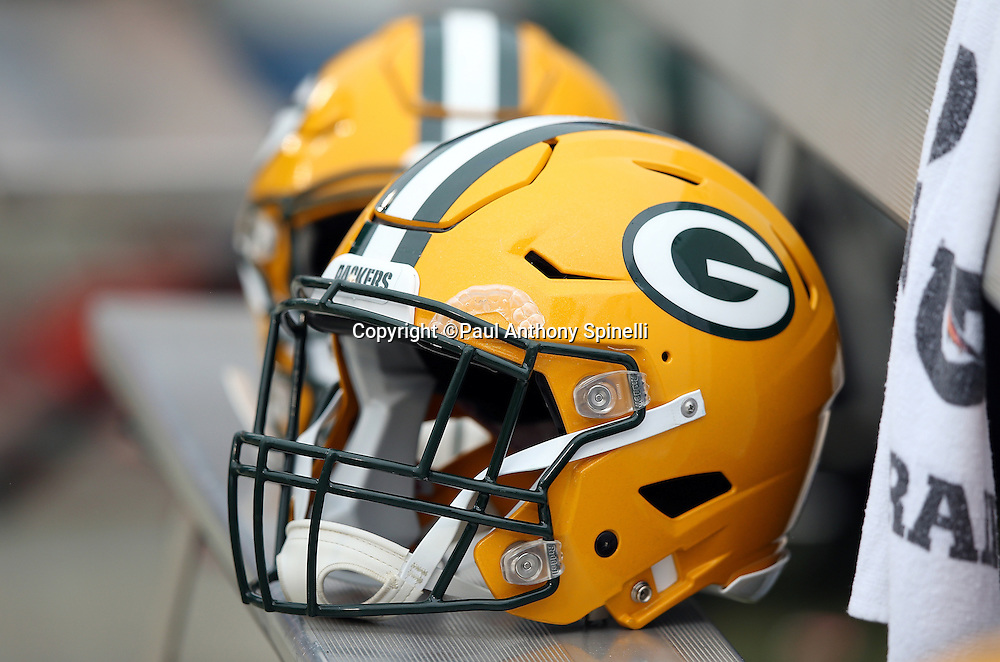 A pair of Green Bay Packers helmets sits on the sideline bench during the 2015 week 15 regular season NFL football game against the Oakland Raiders on Sunday, Dec. 20, 2015 in Oakland, Calif. The Packers won the game 30-20. (©Paul Anthony Spinelli)