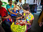 25 NOVEMBER 2017 - YANGON, MYANMAR: A woman sells green mango as a snack on the Yangon Circular Train. The Yangon Circular Train is a 45.9-kilometre (28.5 mi) 39-station two track loop system connects satellite towns and suburban areas to downtown. The train was built during the British colonial period, the second track was built in 1954. Trains currently run both directions (clockwise and counter-clockwise) around the city. The trains are the least expensive way to get across Yangon and they are very popular with Yangon's working class. About 100,000 people ride the train every day. A a ticket costs 200 Kyat (about .17¢ US) for the entire 28.5 mile loop.    PHOTO BY JACK KURTZ