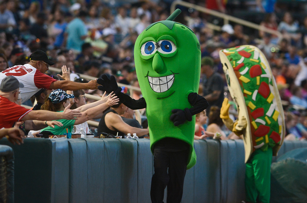 mkb061617e/sports//Marla Brose --  The Green Chile mascot gets high fives after beating the Taco mascot in a running race between innings during Friday night's baseball game between the Albuquerque Green Chile Cheeseburgers and the Fresno Tacos, June 16, 2017, at Isotopes Park in Albuquerque, N.M. The  Albuquerque Green Chile Cheeseburgers took the field for one night only.  (Marla Brose/Albuquerque Journal)