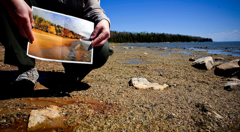 Michelle Hefty, Park Maager of Newport State Park along Lake Michigan, holds a picture of the once pristine beach before the Cladophora moved in and covered it. Invasive species in the great lakes are the reason for the Cladophora the that is hitting beaches all over Lake Michigan.