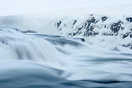 The waterfall Gullfoss of the river Hvita with ice formations on a cloudy day in the winter, vally Haukadalur, Iceland