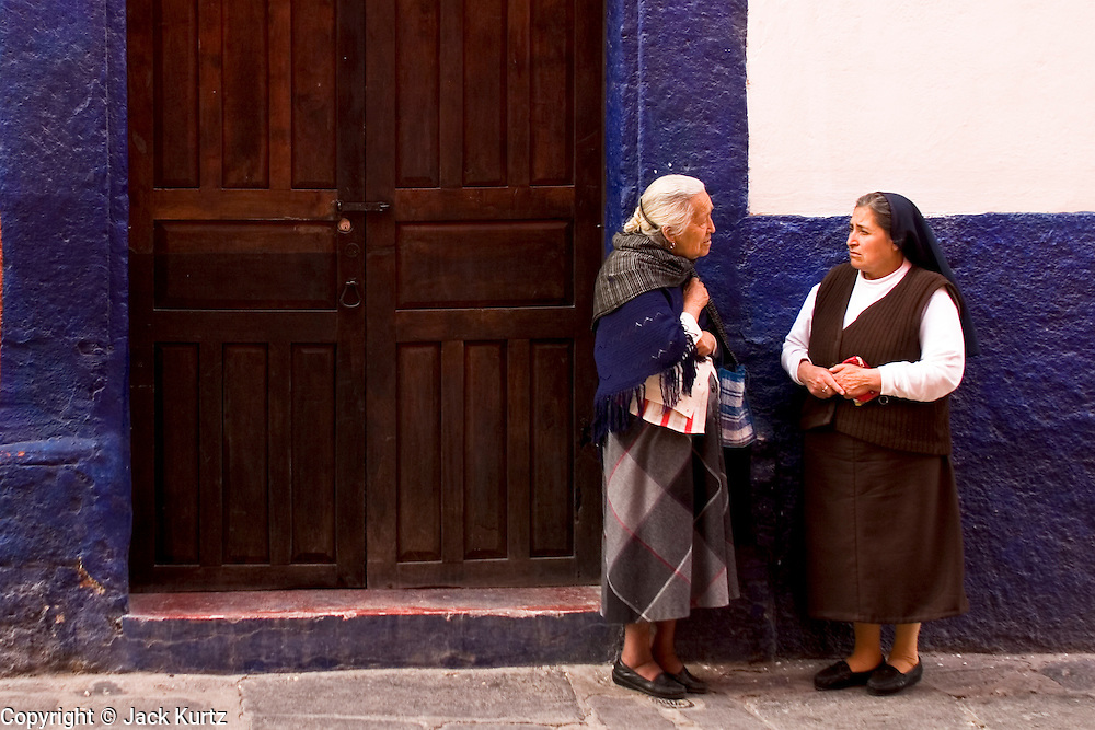 03 APRIL 2004 - SAN MIGUEL DE ALLENDE, GUANAJUATO, MEXICO: A parishioner and a nun chat in a doorway in San Miguel de Allende, Mexico. San Miguel, which was founded in the 1600s, is one of Mexico's premier colonial cities. It has very strict zoning and building codes meant to preserve the historic nature of the city center. About 7,500 US citizens, mostly retirees, live in San Miguel. PHOTO BY JACK KURTZ