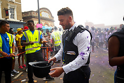 © Licensed to London News Pictures. 28/08/2016. London, UK. A police officer reacts after getting hit by paint whilst dancers and children parading on family day of Notting Hill Carnival in west London, Sunday, 28 August 2016. Photo credit: Tolga Akmen/LNP