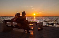 THEMENBILD - URLAUB IN KROATIEN, ein Touristen Paar sitzt auf einer Bank und genießt den Sonnenuntergang an der Strand Promenande, aufgenommen am 03.07.2014 in Porec, Kroatien // a tourist couple sitting on a bench and enjoying the sunset at the beach promenades, at Porec, Croatia on 2014/07/03. EXPA Pictures © 2014, PhotoCredit: EXPA/ JFK
